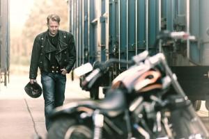 Porträtfoto eines Bikers mit seinem Harley Davidson Motorrad