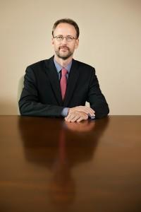 Dieses Porträtfoto zeigt einen Geschäftsmann an einem Konferenztisch.