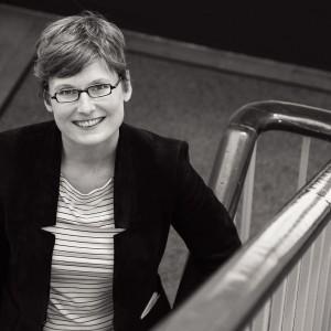 Dieses Foto zeigt die Mitarbeiterin einer Universität in einem Treppenhaus.