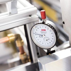 Ein sehr empfindliches Messgerät mit analogem Display, das die präzise Arbeitsweise einer Maschine für Kontrollzwecke anzeigt.