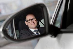 Porträtfoto eines Geschäftsmanns, der sich im Rückspiegel seines Autos spiegelt.