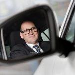Business Porträtfoto: Mann in Anzug blickt in den Rückspiegel eines Autos.