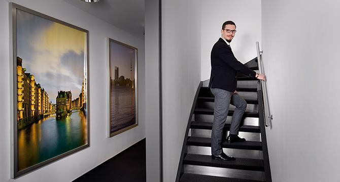 Porträtfoto aus Hamburg: Junger Mann in Businesskleidung geht eine Treppe hinauf.