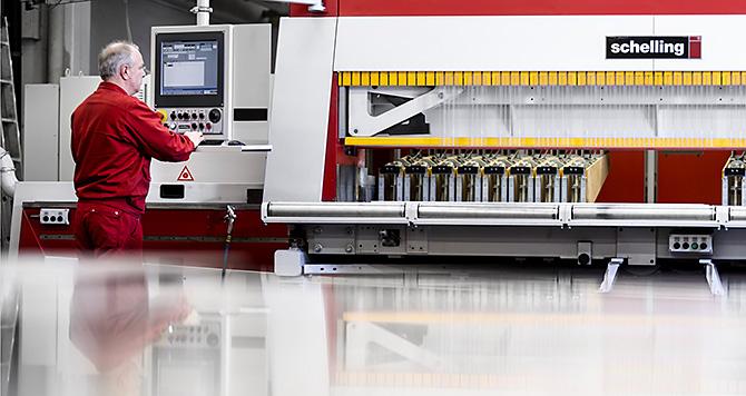 Dieses Industriefoto zeigt einen Mitarbeiter an einer Sägemaschine.