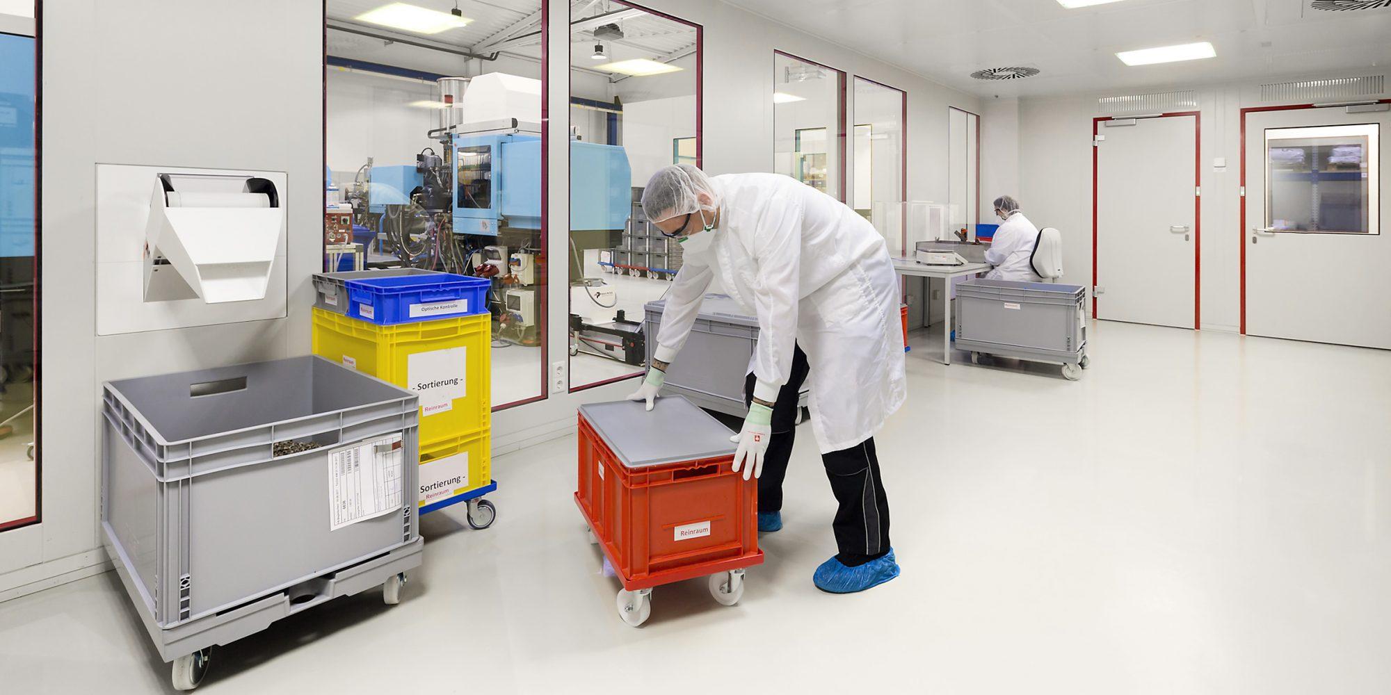 Mitarbeiter verarbeiten in dem Reinraum eines Industrieunternehmens frisch produzierte Kunststoffteile für die Luftfahrtindustrie.