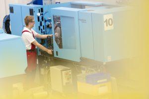 Arbeiter an einer Spritzgussmaschine in einem Industrieunternehmen in Hamburg.