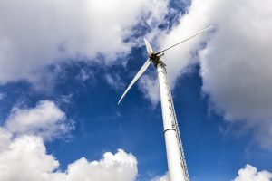 Windkraftanlage vor blauem Himmel.