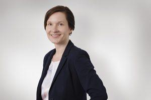 Mitarbeiterfoto zeigt eine Geschäftsfrau in einem Fotostudio vor weißem Hintergrund mit Schattenwurf.