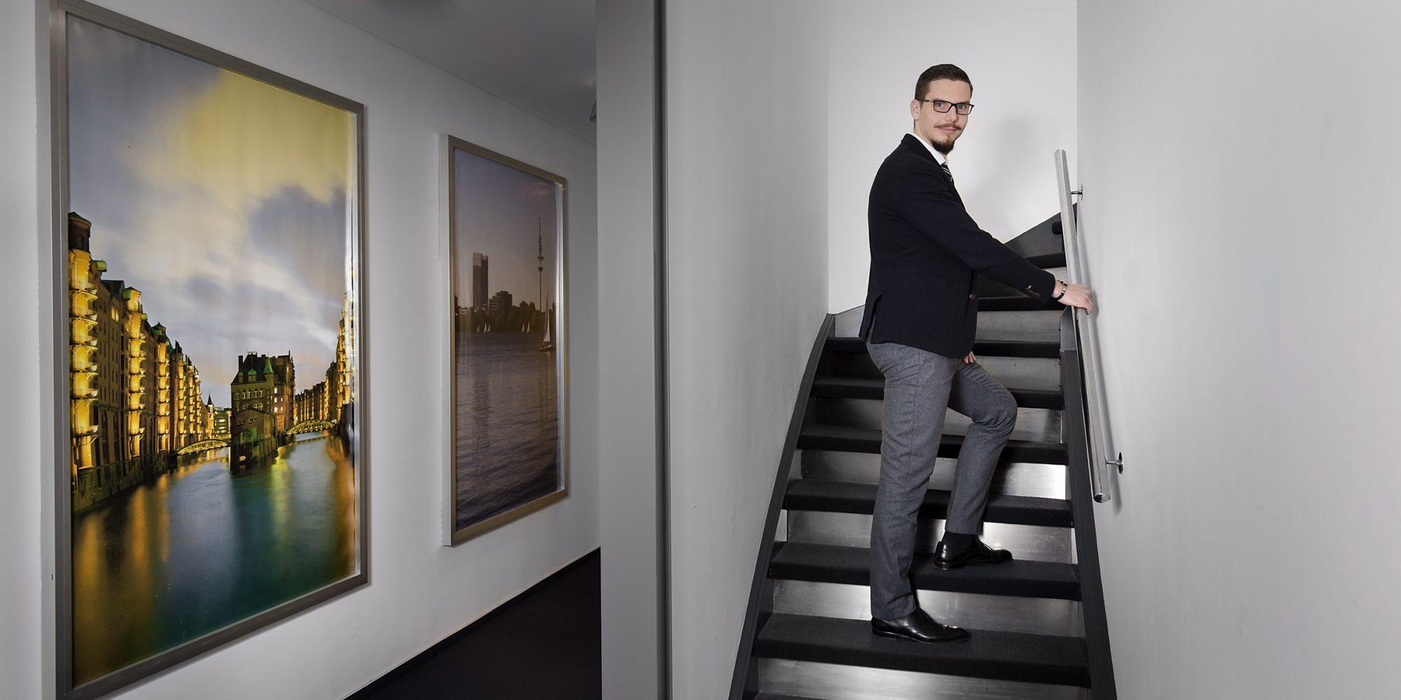 Mitarbeiterfoto eines Mannes in einem Treppenhaus mit Hamburger Bildmotiven an den Wänden.