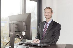Porträtfoto eines Geschäftsführers am Schreibtisch seines Büros.