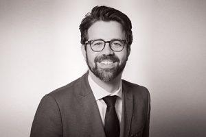 Porträtfoto eines Geschäftsmannes in schwarzweiss mit leichter Farbtönung.