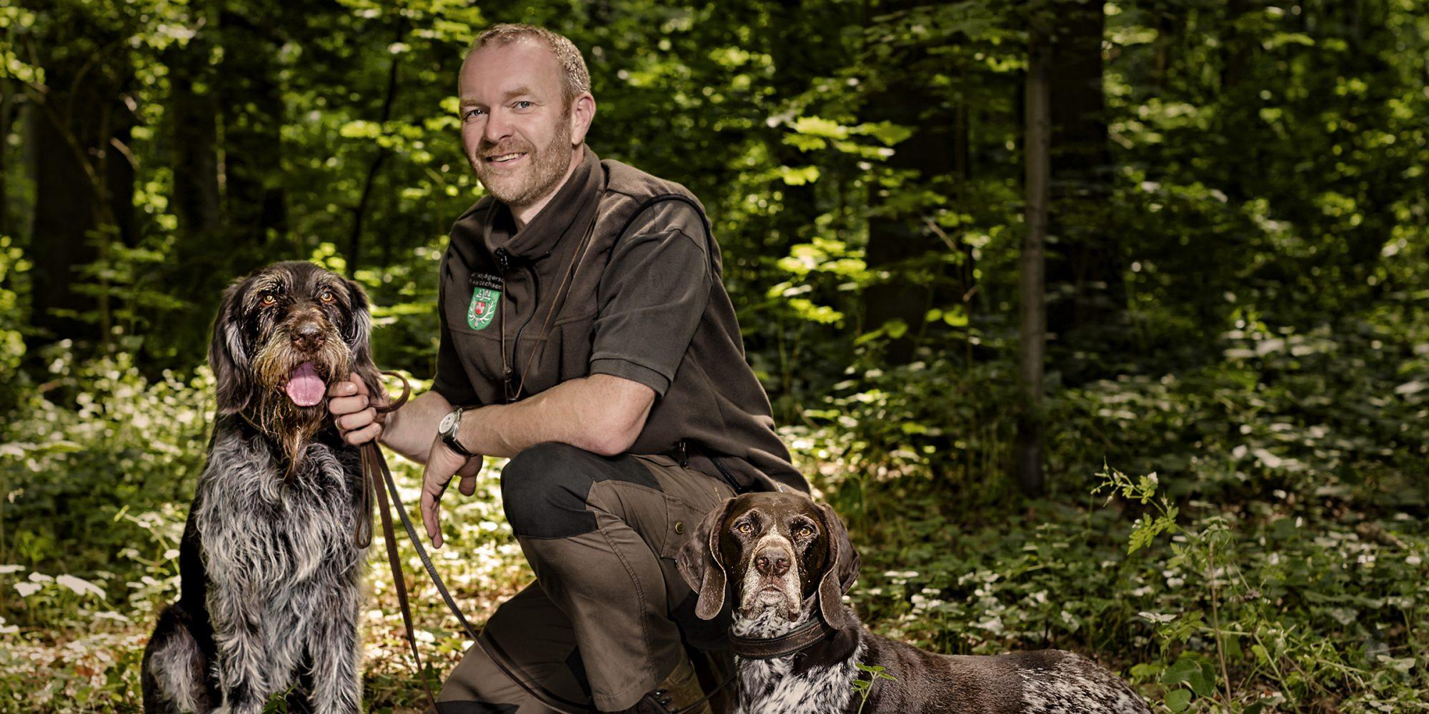 Dieses Porträtfoto zeigt einen Jäger zusammen mit seinen Jagdhunden.