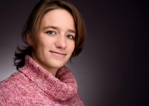 Porträtfotografie einer jungen Frau im Fotostudio vor dunklem Hintergrund