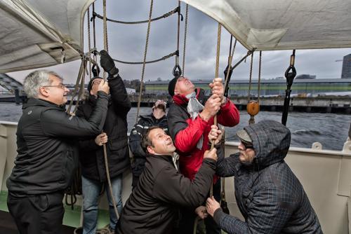 Teilnehmer einer Veranstaltung auf einem Segelschiff im Hamburger Hafen