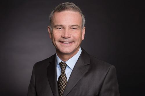 Porträtfoto eines Managers vor schwarzem Hintergrund im Fotostudio
