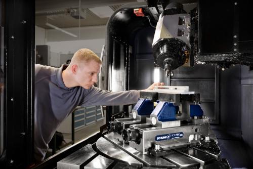 Arbeiter an einer Fräsmaschine.