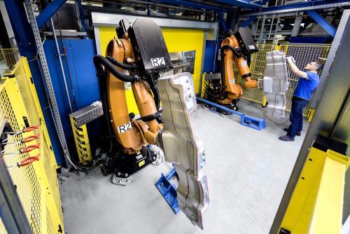Mensch und Maschine: KUKA Roboter und ein Werksmitarbeiter in der Automobilindustrie. Copyright: Fotograf Bernhard Classen aus Hamburg.