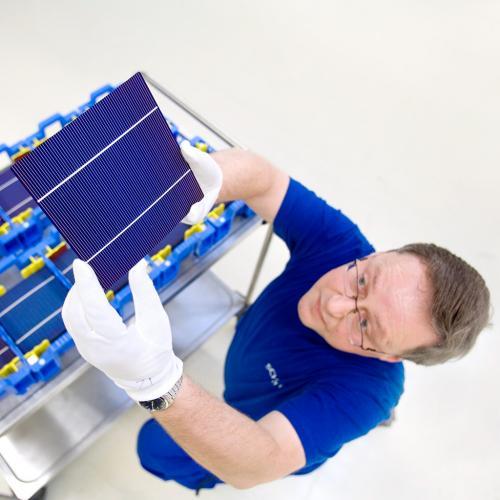 Mitarbeiter betrachtet eine fertige Solarzelle.