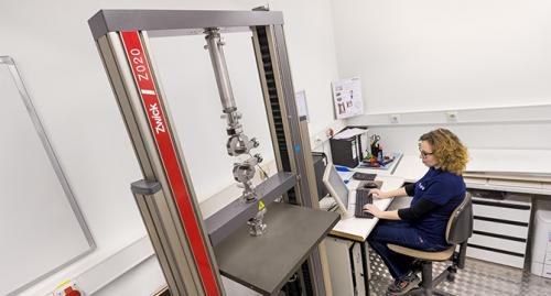 Mitarbeiterin eines Instituts untersucht an einer Maschine die Reissfestigkeit von Verpackungsmaterial.