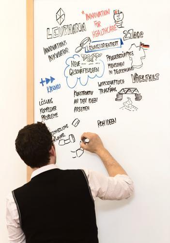 Während einer Veranstaltung schreibt der Redner Notizen an eine Tafel.