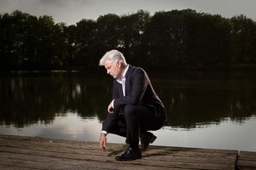Porträtfoto eines Managers mit mobiler Blitzanlage an einem See