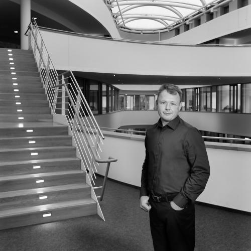 Dieses Mitarbeiterfoto zeigt einen Mitarbeiter in einem modernen Bürogebäude.