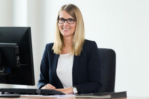Mitarbeiterfoto einer Mitarbeiterin an ihrem Schreibtisch im Büro.
