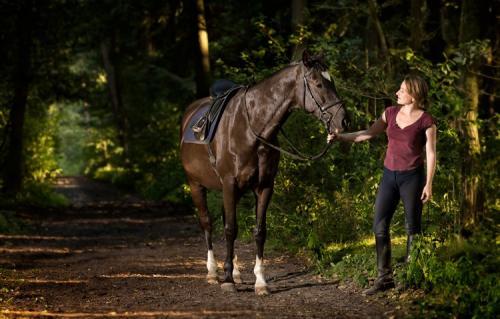 Fotografie einer Reiterin gemeinsam mit Pferd auf einem Waldweg