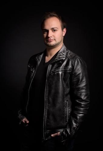 Dieses Porträtfoto zeigt einen jungen Mann in dunkler Umgebung im Fotostudio.