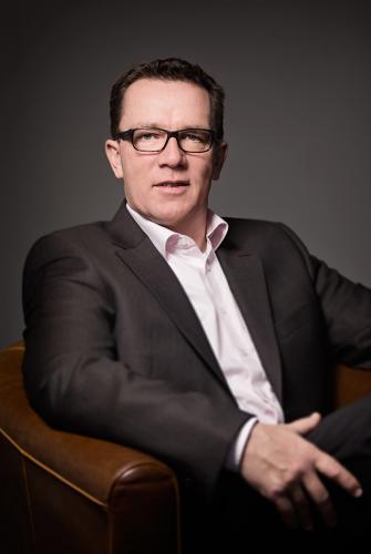 Dieses Porträtfoto zeigt einen Geschäftsmann in einem Sessel sitzend.