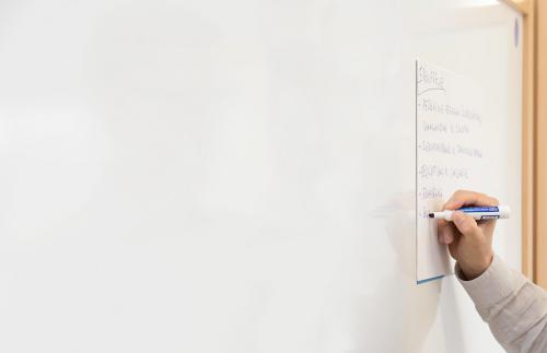 Ein Veranstaltungsteilnehmer macht sich Notizen auf einem zettel.
